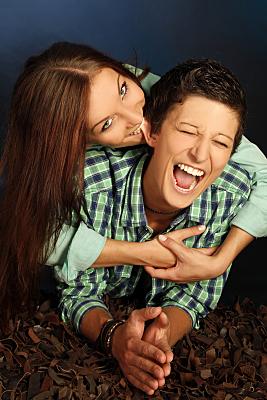 Paarportrait vor dunklem Hintergrund, auf dem beide nach vorn gelehnt in Richtung Kamera schauen, während die Frau von hinten über die Schulter schaut und der vorderen Person ins Ohr beißt.
