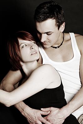 Low-Key Portrait eines Paares, auf dem die Frau rücklings am Mann lehnt und ihn über ihre Schulter hinweg sinnlich anschaut.