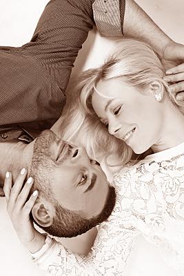 Portrait eines Paares aus der Vogelperspektive, bei dem beide Kopf an Kopf auf dem Rücken liegend die Gesichter verliebt zueinander gewandt haben.