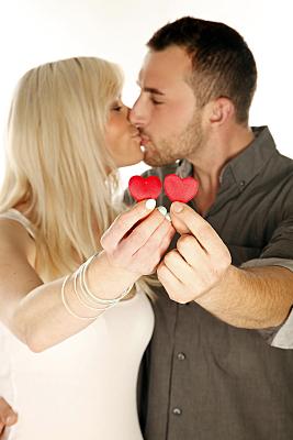 Portraitaufnahme eines Paares, die unscharf im weißen Hintergrund stehen, während beide jeweils ein kleines rotes Herz in den Fokus der Kamera halten.