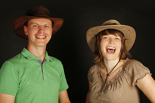 Portrait eines Paares vor schwarzem Hintergrund, auf dem beide Personen Krempenhüte tragen und offen in die Kamera lachen.