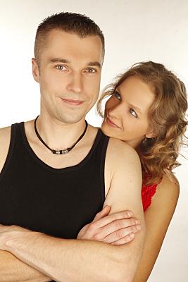 Portrait eines jungen Paares, bei dem der Mann mit verschränkten Armen im Vordergrund steht, während die Frau seitlich von hinten über seine Schulter zu ihm hochblickt.