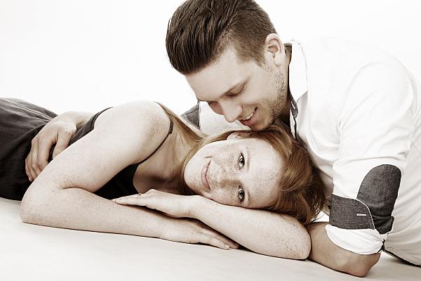 Helles sepiafarbenes Portrait eines Paares, auf dem die Frau mit dem Kopf zur Kamera gewandt liegt, während der Mann über sie gebeugt herabschaut.