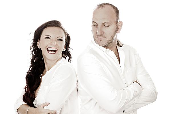 Seitliches High-Key Portrait eines Paares in weißen Oberteilen, bei dem die Frau lachend über ihre Schulter an der Kamera vorbeischaut, während der Mann in ihre Richtung blickt.