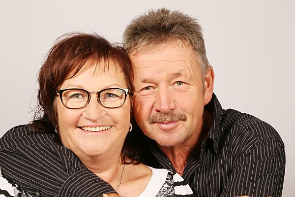 Kopfportrait eines Paares, das gemeinsam in die Kamera blickt, wobei der Mann seinen Arm von hinten über die Schulter der Frau gelegt hat.