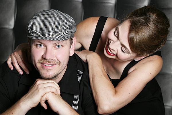Nahaufnahme eines Paarportraits, auf dem der Mann mit einer Schiebermütze in die Kamera schaut, während die Frau ihn verliebt von hinten über seine Schulter anschaut.