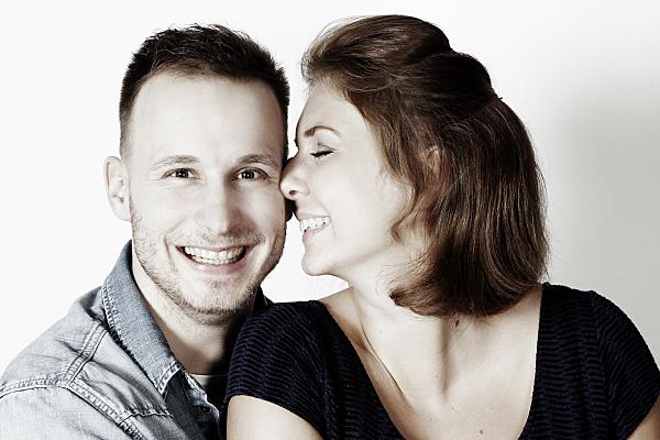 Portrait eines jungen Paares, bei dem der Mann offen lächelnd in die Kamera blickt, während die Frau mit geschlossenen Augen zu ihm gewandt an seiner Wange lehnt.
