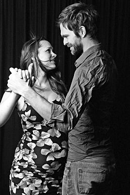 Schwarz-weißes seitliches Portrait eines tanzenden Paares, welches sich verliebt anschaut.