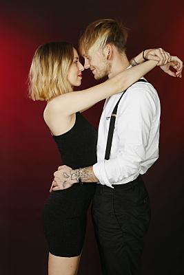 Seitliches Portrait eines jungen Paares vor rotem Hintergrund, welches verliebt zueinandern gewandt steht.