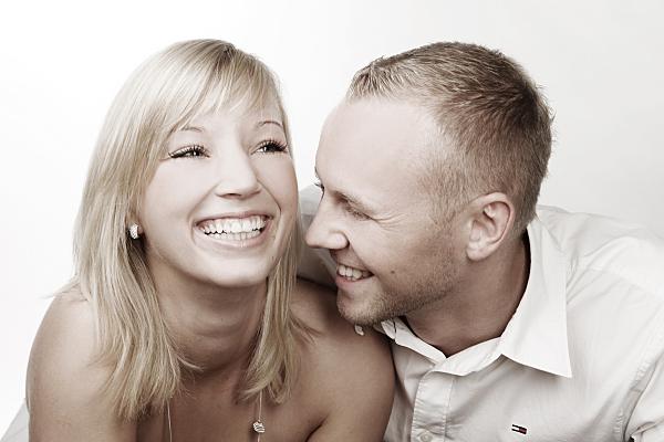 Portrait eines jungen, fröhlichen Paares, bei dem die Frau lachend in die Ferne blickt, während der Mann sie von der Seite her anschaut.