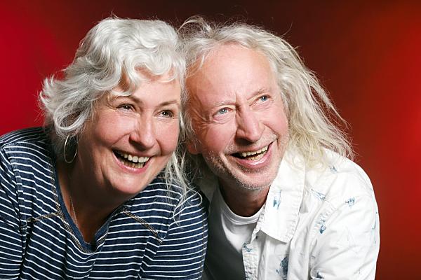 Portrait eines älteren, weißhaarigen Paares vor rotem Hintergrund, das lachend in die Ferne blickt.