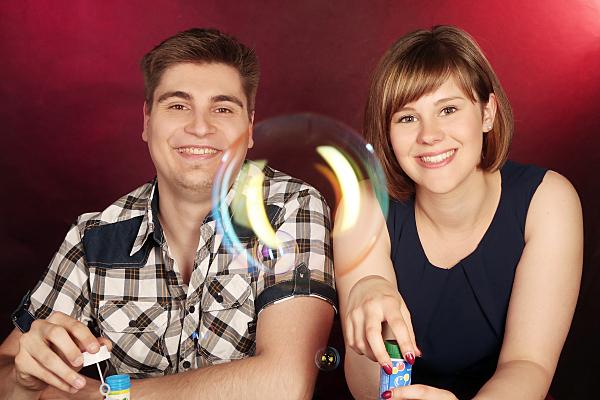 Portrait eines jungen fröhlichen Paares vor rotem Hintergrund mit einer Seifenblase mittig vor der Kamera im Vordergrund.