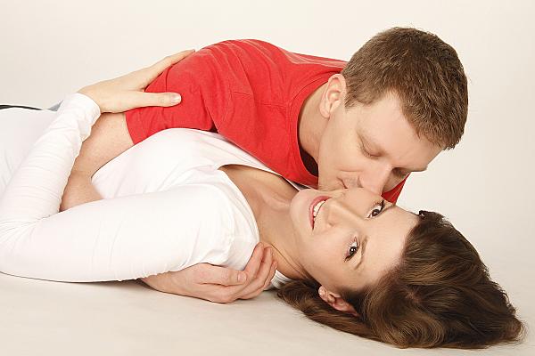 Portrait eines jungen Paares, bei dem die Frau auf dem Rücken liegend in die Kamera lächelt, während der Mann sie auf die Wange küsst.