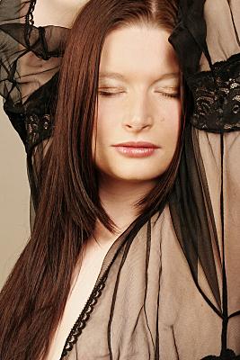 Erotikfoto junge Frau mit geschlossenen Augen und durchsichtigem Tüllmantel, die ihre Arme über den Kopf hebt und ihren Kopf leicht zur Seite neigt.