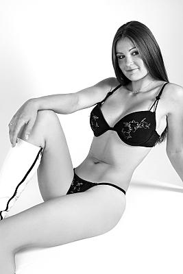 Erotikfoto sitzende und sich nach hinten lehnende, junge Frau mit schwarzer Reizwäsche und weißen Stiefeln.