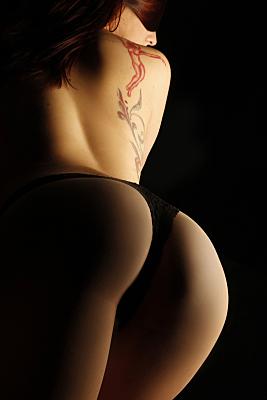 Erotikfoto tätowierte, rothaarige Frau mit schwarzem String und vorgerecktem Po in Rückansicht.