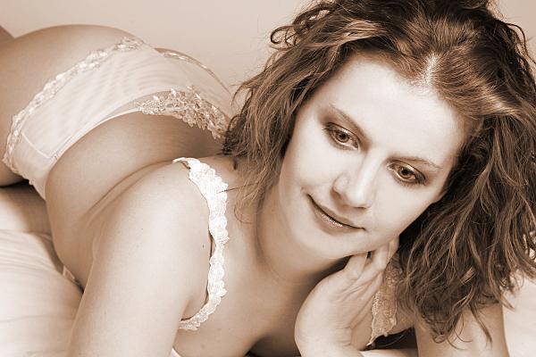 Sepiafarbenes Erotikfoto liegende Frau in heller Reizwäsche mit einer Hand am Hals.