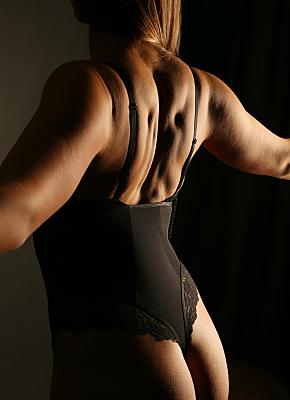 Erotikfoto Frauenrücken mit dunklem Body in Rückansicht.