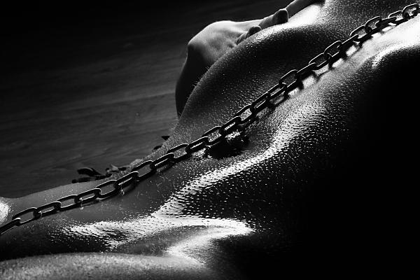 Schwarz-weiß Erotikfoto liegende, nackte Frau mit öligem Körper und Gliederkette von Hals bis zu den Beinen gelegt.