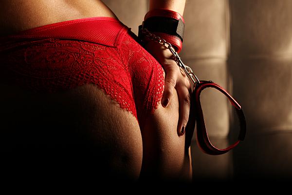 Erotikfoto Frauenpo in rotem String und mit roten Handschellen fässt sich an eine Pobacke.