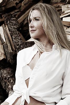 Erotikfoto Frau mit langen, blonden Haaren steht mit weißer, geöffneter Bluse vor Baumstämmen.