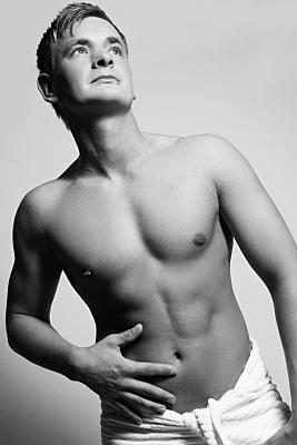 Schwarz-weißes Erotikfoto eines jungen Mannes, oberkörperfrei mit Handtuch um den Hüften, links über die Kamera blickend.