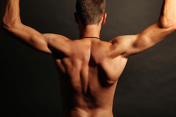 Low-Key Erotikfoto eines Mannes, von hinten, mit erhobenen Armen.