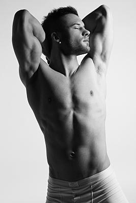 Schwarz-weißes Erotikfoto eines oberkörperfreien Mannes, der mit hinter dem Nacken verschränkten Armen nach links ins Licht schaut.