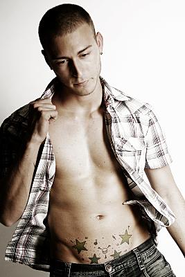 Erotikfoto eines Mannes mit offenem, kariertem Hemd und Sterntattoos am Unterbauch, der eine Hand am Kragen hat und nach unten schaut.