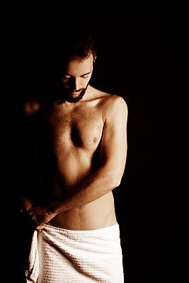 Low-Key Erotikfoto eines oberkörperfreien Mannes mit weißem Handtuch um den Hüften, welcher nach unten blickt.
