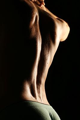 Erotikfoto eines Mannes von hinten mit hinter dem Hals verschränkten Händen.