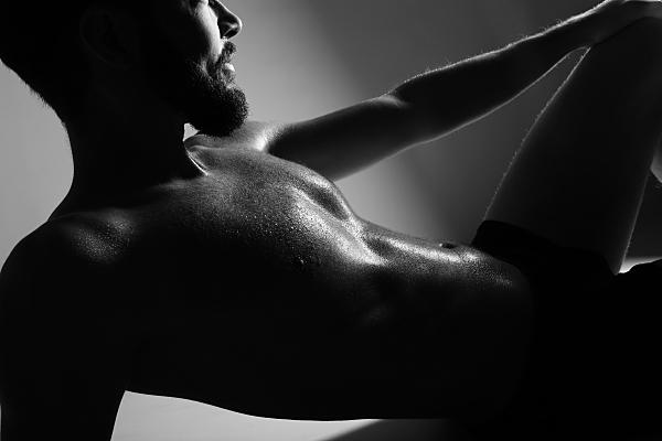 Low-Key Nahaufnahme Erotikfoto eines Mannes, seitlich liegend, mit zum Teil abgeschnittenem Kopf