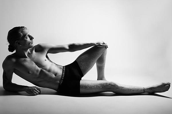 Schwarz-weißes, seitliches Ganzkörper Erotikfoto eines Mannes, der auf dem Rücken liegt, vom rechten Arm hochgestützt, linkes Bein angewinkelt aufgestellt und den linken Arm darauf abgesützt.