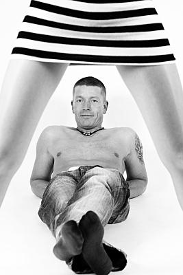 Schwarz-weißes Erotikfoto Paar, auf dem im Vordergrund eine kurzberockte Frau mit gespreitzten Beinen steht, zwischen denen im Hintergrund der Mann mit Jeans und nacktem Oberkörper liegt und in ihre R
