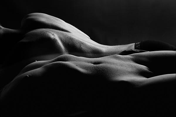 Schwarz-weißes Erotikfoto Paar, bei dem im Hintergrund der Rücken eines nackten Männeroberkörpers mit dunkler Shorts und im Vordergrund die Vorderansicht einer nackten Frau zu sehen ist.