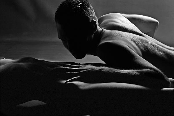 Schwarz-weißes Erotikfoto Paar, bei dem der bäuchlings liegende nackte Mann über den nackten Körper der Frau streicht.