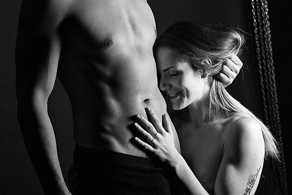 Schwarz-weißes Erotikfoto Paar, bei dem der Mann mit nacktem Oberkörper und schwarzer Boxershorts den Kopf der lächelnden Frau an seinen Oberkörper drückt.
