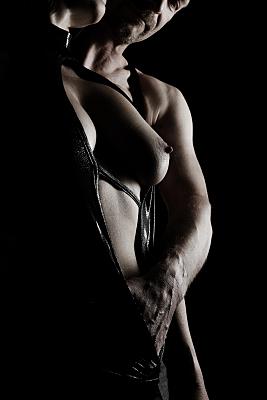 Erotikfoto hintereinander stehendes Paar, auf dem der Mann in den geöffneten, die Sicht auf eine Brust freigebenden, schwarzen Body der vorne stehenden Frau greift.