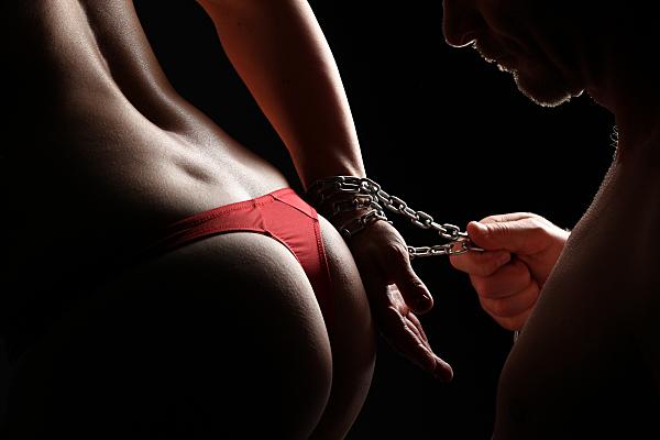 Erotikfoto Paar, bei dem die Rückansicht einer Frau in rotem String mit einer Kette ums Handgelenk, die der Mann festhält und dabei auf ihren Po schaut, zu sehen ist.