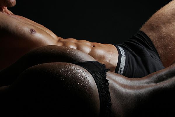 Erotikfoto Paar, bei dem im Hintergrund ein nackter Männeroberkörper mit dunkler Shorts und im Vordergrund ein nackter Frauenrücken und Po mit schwarzem String zu sehen ist.