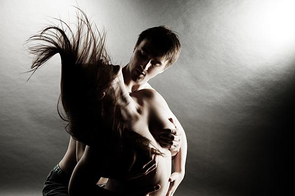 Schwarz-weißes Erotikfoto Paar, bei dem die Frau mit nacktem Oberkörper vor dem Mann steht und ihre Haare schwungvoll nach hinten wirft, während der Mann sie ansieht und ihre Brüste mit seinen Händen