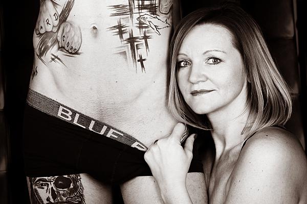 Schwarz-weißes Erotikfoto Paar eines tätowierten Mannes in dunkler Boxershorts und nacktem Oberkörper neben dem eine Frau kniet, die seine Unterhose leicht nach unten zieht.