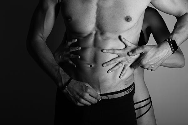 Schwarz-weißes Erotikfoto Paar, bei dem die Frau in knapper Unterhose von hinten den Mann in schwarzer Boxershorts mit nacktem Oberkörper umfässt und er dabei ihre Hand hält.