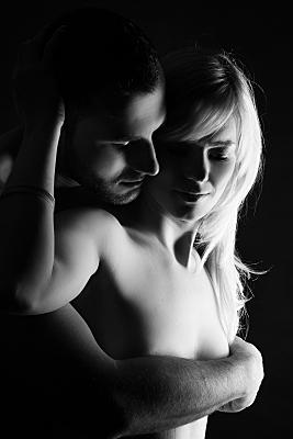 Schwarz-weiß Erotikfoto Paar, bei dem der Mann die blonde Frau von hinten umarmt und mit seinem Arm ihre Brust verdeckt.