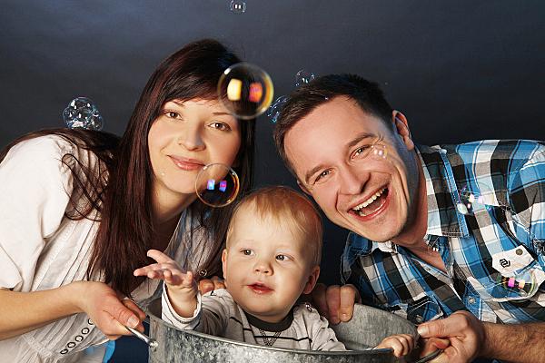 Familienfoto Eltern und Kind, die Seifenblasen hinterherschauen.