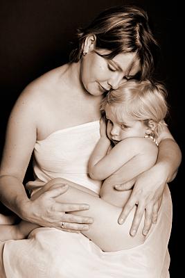 Low Key Familienfoto einer Mutter in Schulterfreiem Bandeau-Top, die ihr Kleinkind vor sich hält.