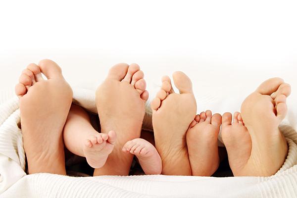 Familienfoto Füße zweier Erwachsener mit Kinderfüßen dazwischen aus einer weißen Decke hervorschauend.