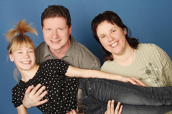 Familienfoto lächelnde Eltern, die ihre Tochter schräg vor sich hochheben vor blauem Hintergrund.