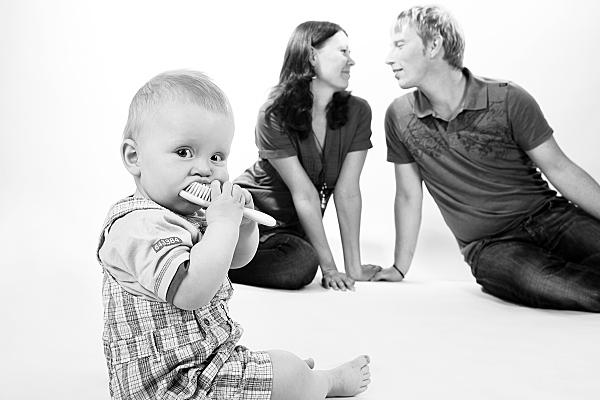 Low Key Familienfoto sich liebevoll anschauender, im Hintergrund sitzender Eltern und im Vordergrund sitzendes Kindes, das eine Bürste in den Mund nimmt.