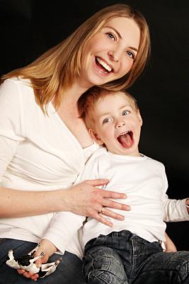 Familienfoto lächelnde Mutter mit lachendem Kind vor sich.